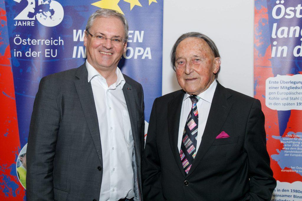 """Landtagspräsident Harald Sonderegger und Alt-Landeshauptmann Martin Purtscher stehen vor den RollUps der EU-Ausstellung """"Wachsen in EUropa"""" in der BH Bludenz."""