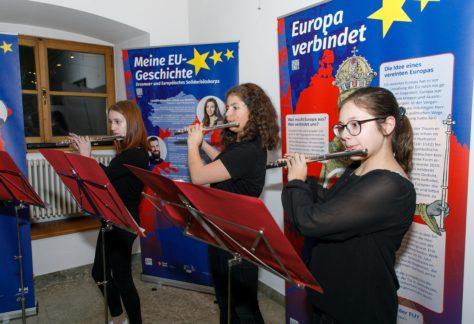 Drei junge Frauen spielen mit ihren Querflöten bei der EU-Ausstellung.
