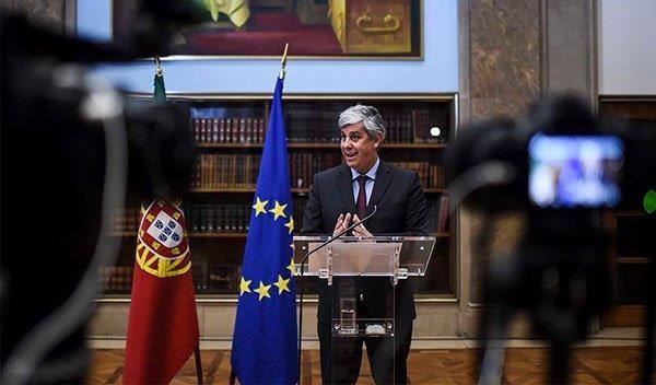 Ein Mann steht am Rednerpult neben einer EU-Flagge.