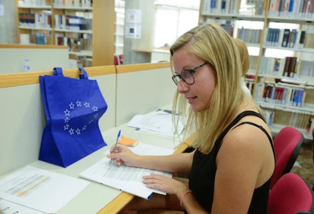 Eine junge Frau sitzt in einer Bibliothek und liest und schreibt dort.