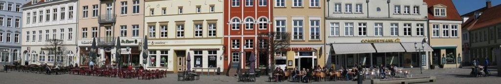 Fußgängerzone mit Straßencafés im Stadtzentrum vor einer Häuserzeile